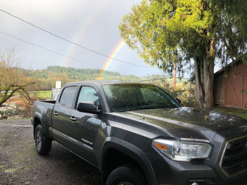 Truck with double rainbow in background